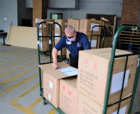Caregiver inspects recent shipment of surgical masks